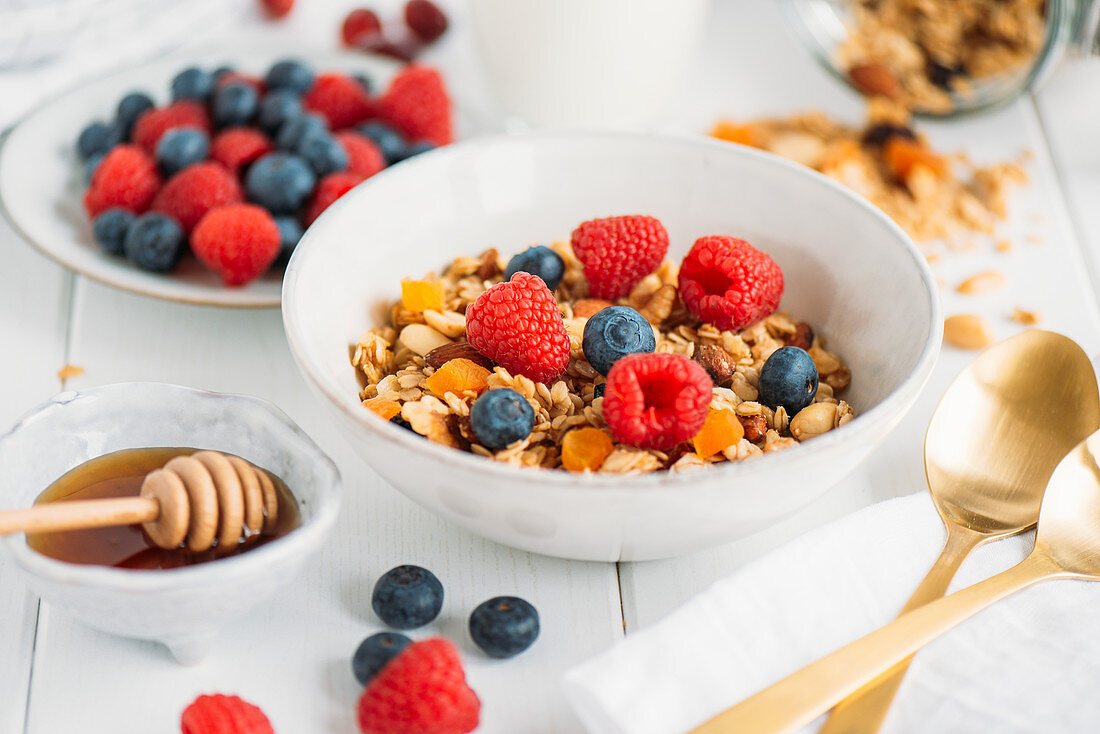 Homemade granola with fresh berries and maple syrup