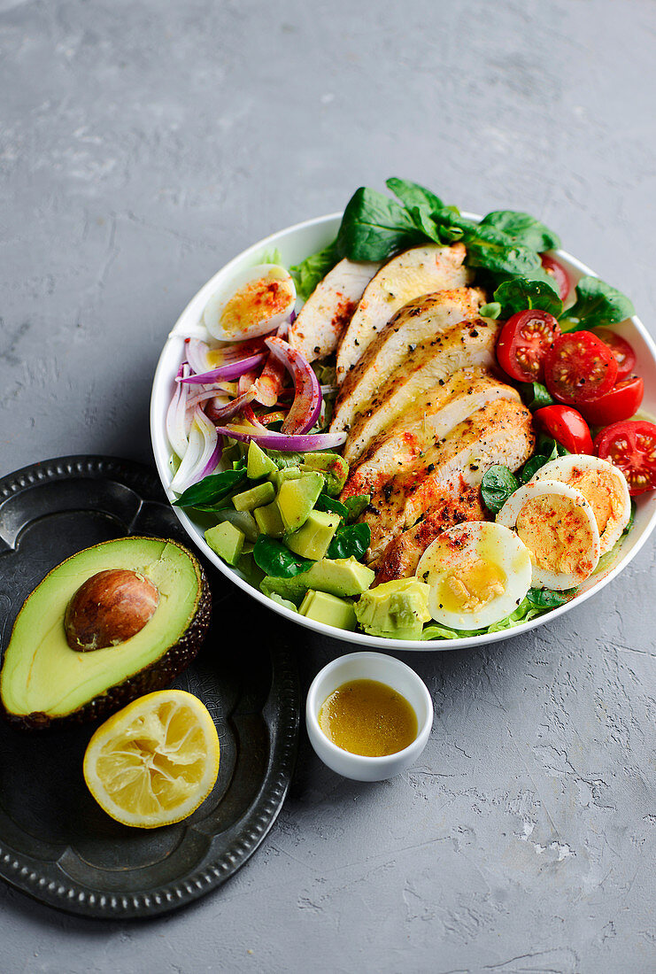 Chicken salad with avocado, eggs and tomatoes