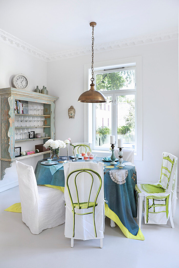 Chairs with loose covers around set table in white dining room
