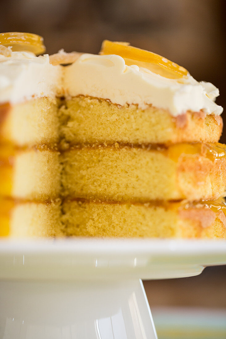 A three-layer lemon cake with frosting, sliced (close-up)