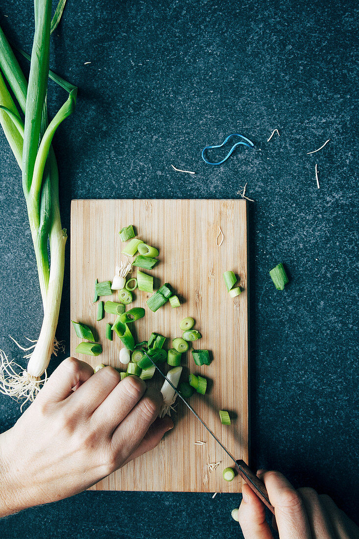 A chef chopping spring onions