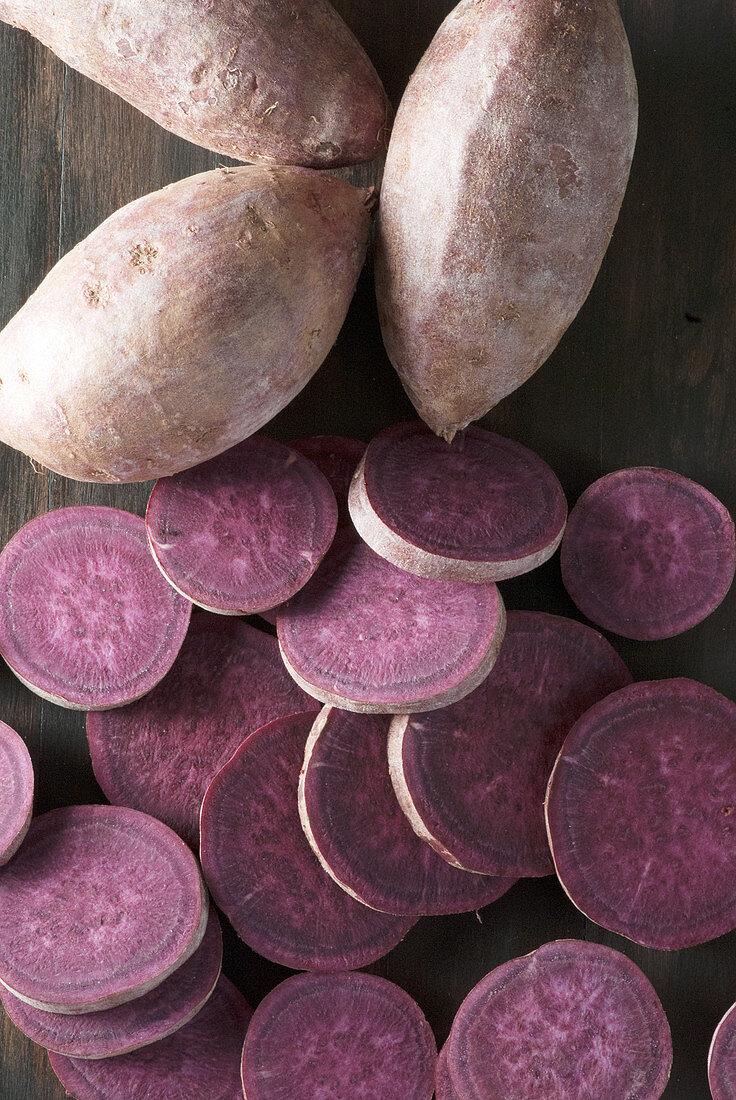 Purple yams sliced on cutting board