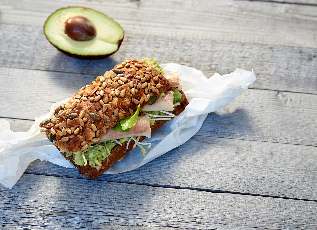A bread roll with smoked trout, sprouts and avocado on paper