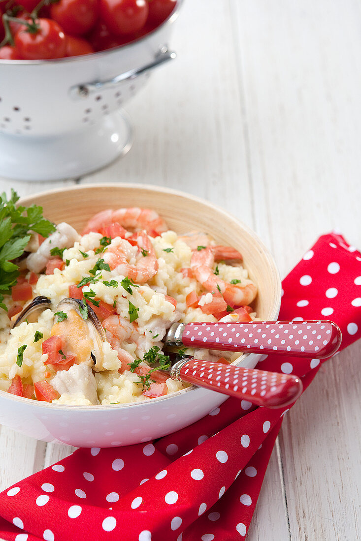 Seafood Risotto – with fish, muscles, prawns and parsley garnish; Cherry tomatoes in background