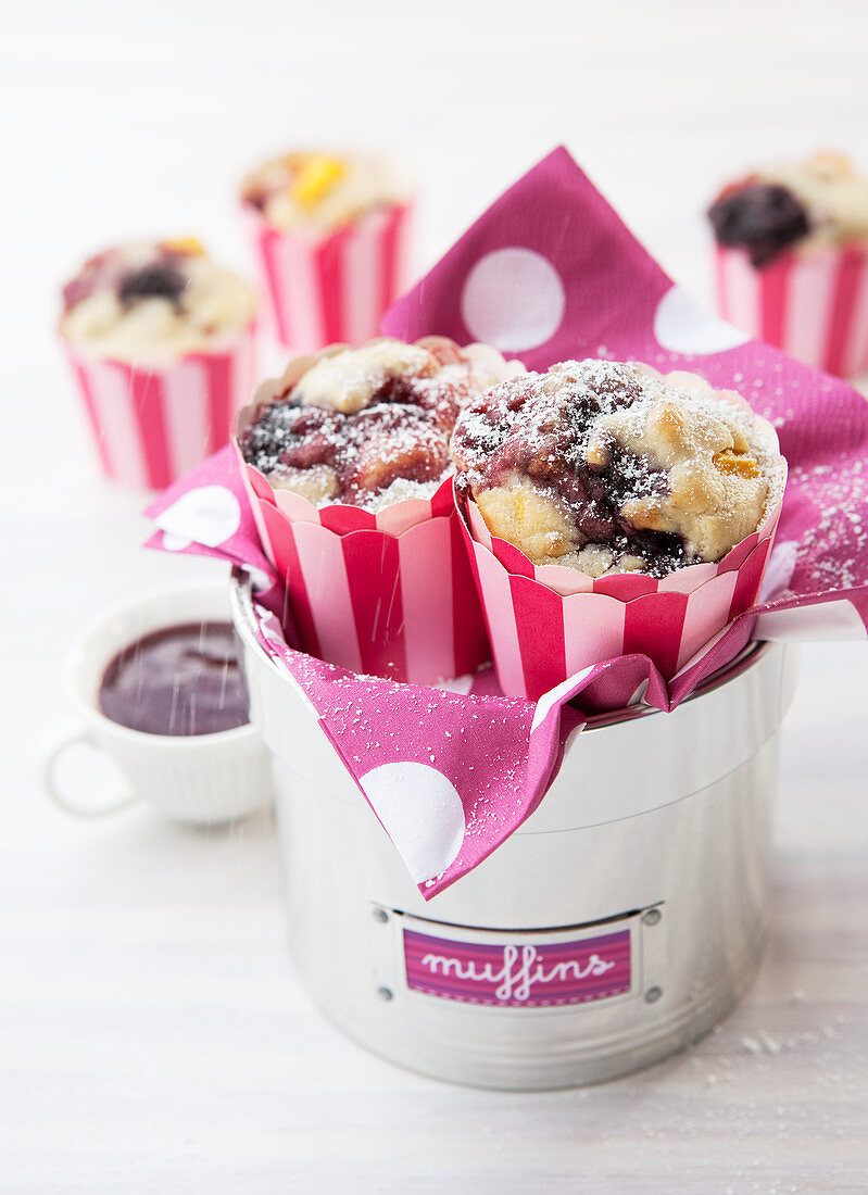 Blueberry and Apple muffins in silver tin sprinkled with icing sugar and raspberry sauce on side
