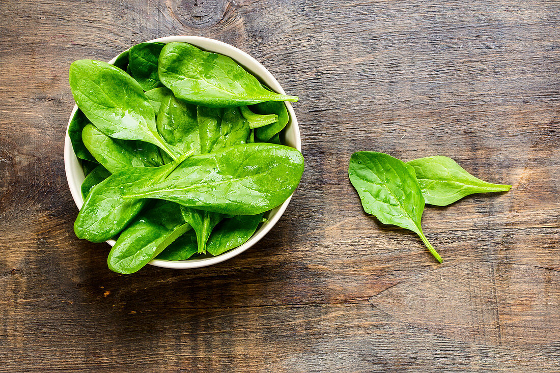 Fresh spinach leaves in a bowl on a wooden background (top view)
