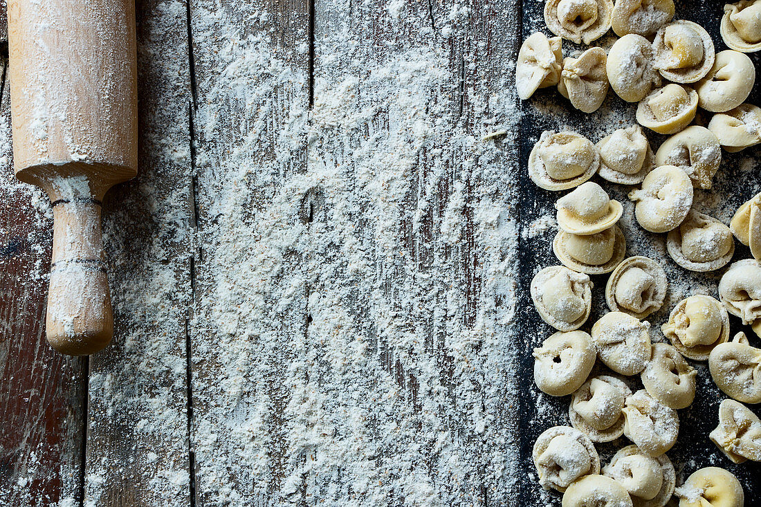 Homemade tortellini with a rolling pin on a floured wooden work surface (top view)