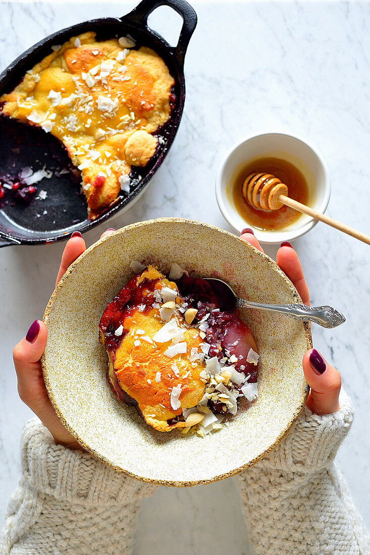 Forest fruits baked under the cake the woman is holding a bowl with breakfast