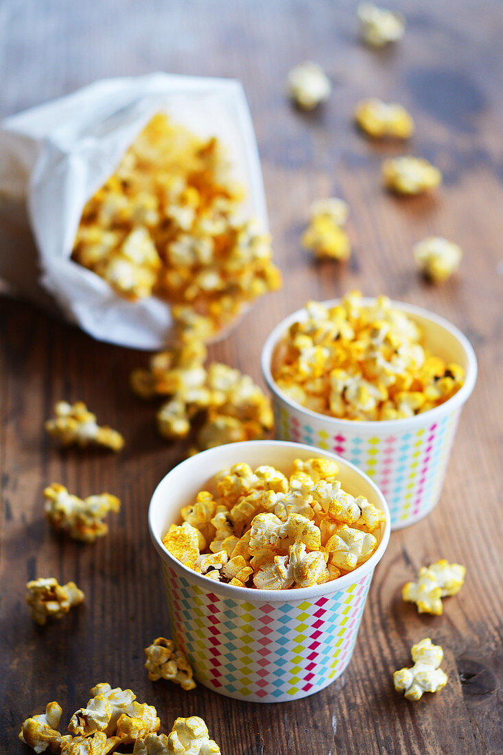 Popcorn with curry and salt in paper cups and a paper bag