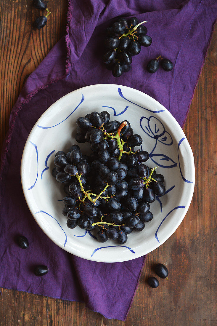Red grapes in a rustic, hand-painted bowl on a wooden table