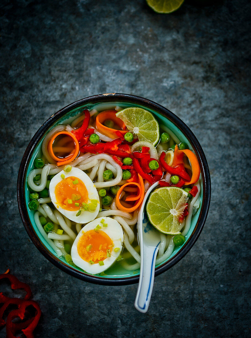 Udon noodle soup with vegetables, lime and eggs