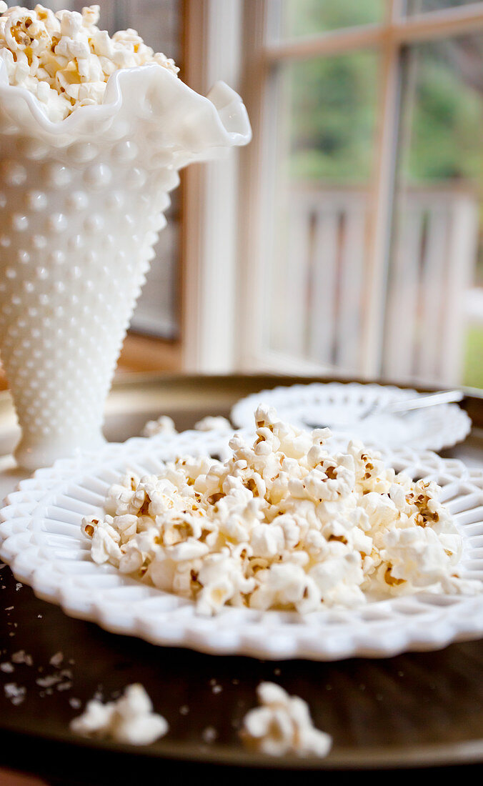 Popcorn sprinkled with sea salt in an antique white dish, with white plates with sea salt and extra popcorn pictured below