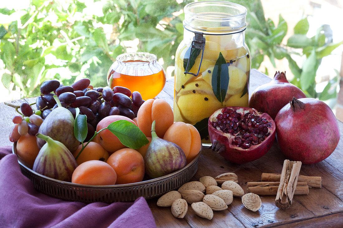 Stillleben mit eingelegten Zitronen, Früchten, Honig, Mandeln und Zimt (Marokko)