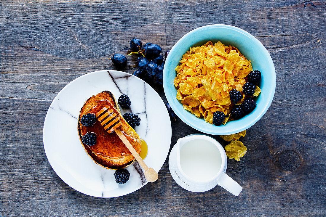 Cornflakes, Toast mit Honig, Milch, Trauben und frische Brombeeren