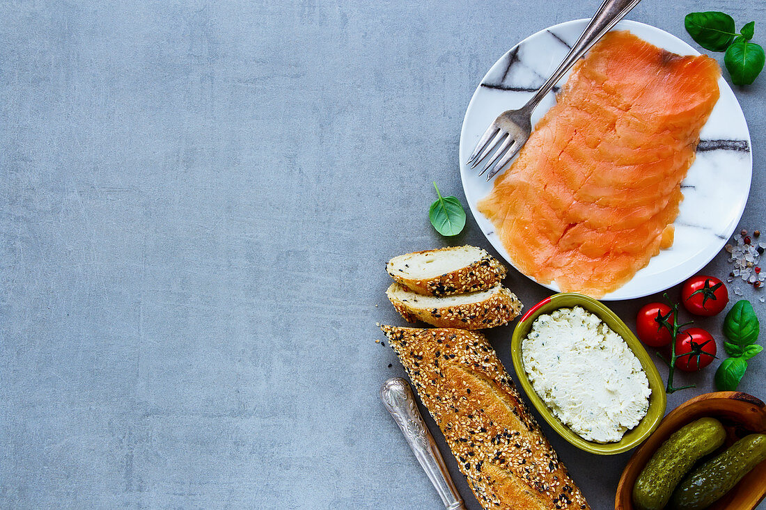 Fresh ingredients for making healthy sandwich. Baguette, smoked salmon, creamcheese, pickles and basil