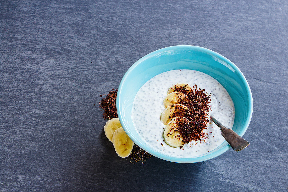 Breakfast almond milk chia seed pudding with banana and chocolate in bowl over grey stone background