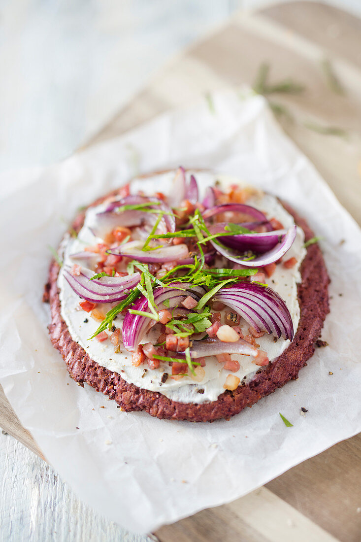Low-carb tart flambée with a beetroot and sunflower seed base, sour cream, bacon and onions