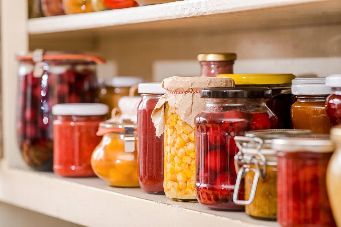 Various jars of preserves on a kitchen dresser