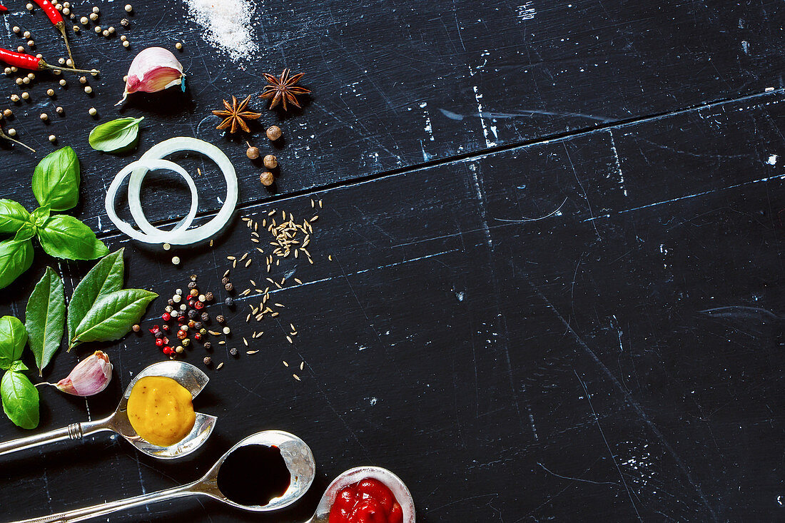 Various sauces in old metal spoons, fresh herbs and spices on dark vintage background with space for text