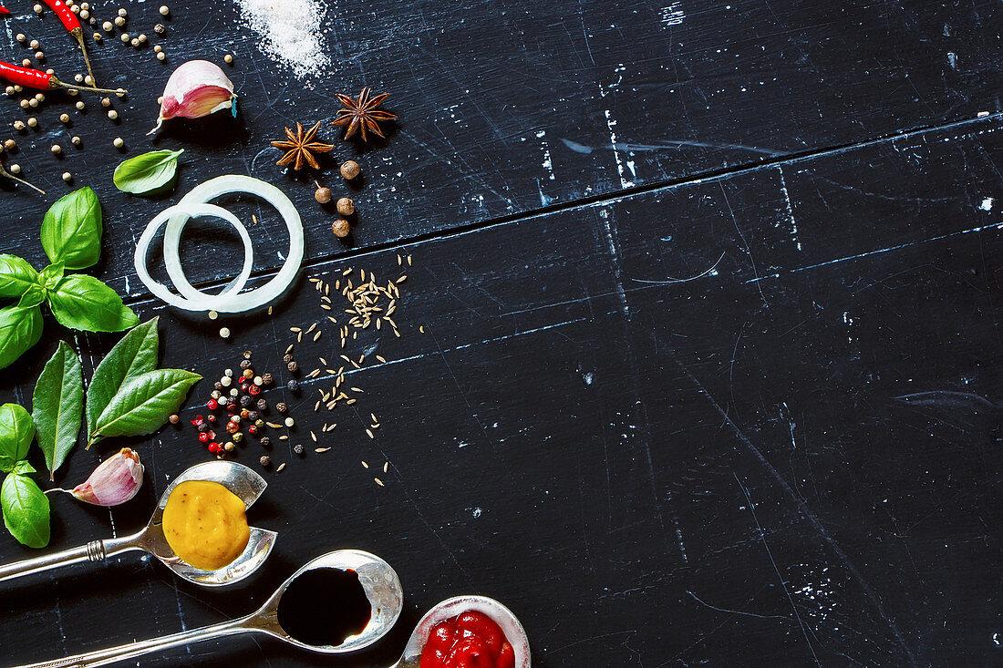 Verschiedene Saucen in alten Metalllöffeln, frische Kräuter und Gewürze
