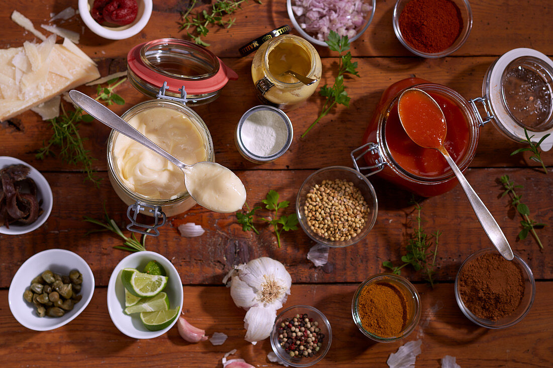 Homemade mayonnaise and ketchup surrounded by ingredients (seen from above)
