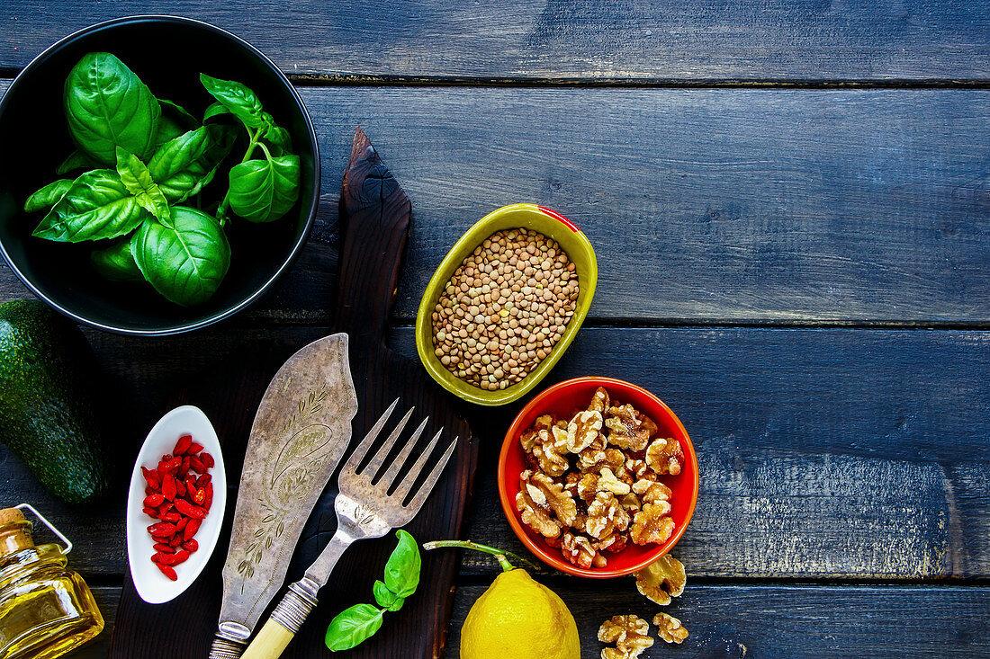 Healthy, vegan, clean eating cooking ingredients. Goji berries, fresh basil, oil, green lentils, avocado, spice, lemon over dark rustic background