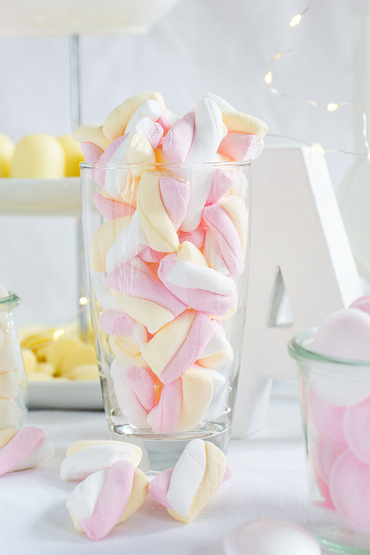 Pink, white and yellow striped marshmallows in a jar