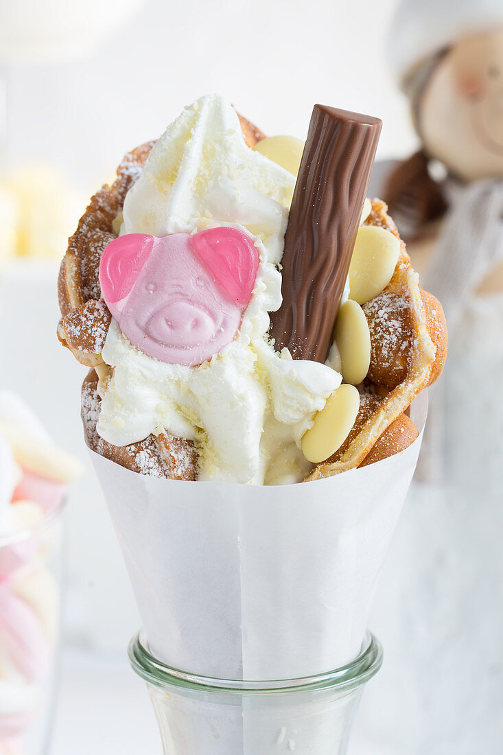 A bubble waffle with a gummy pig sweet, white chocolate and a chocolate bar