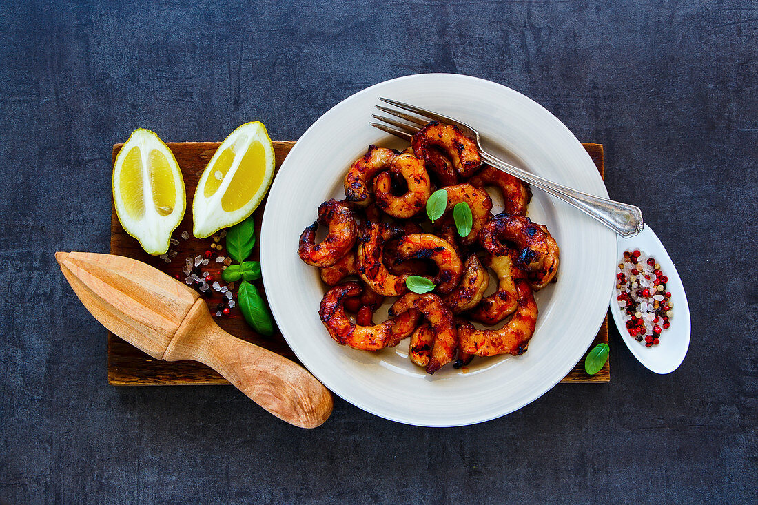 Grilled prawns in white plate with lemon, soy sauce and spices on wooden board over dark vintage stone background