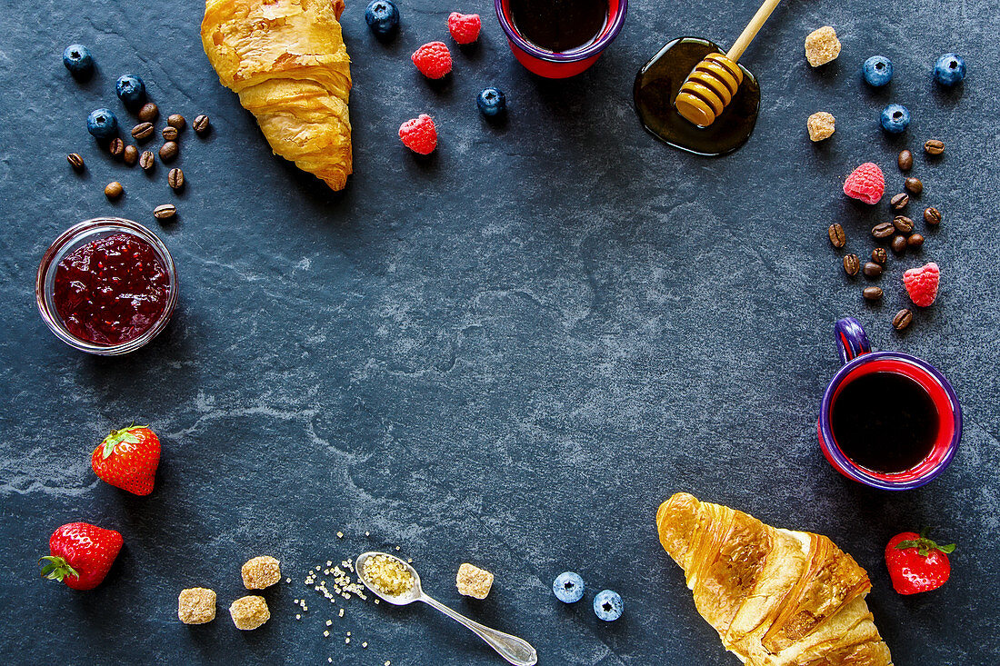 Summer berries, fruit jam, coffee and croissants on dark stone background
