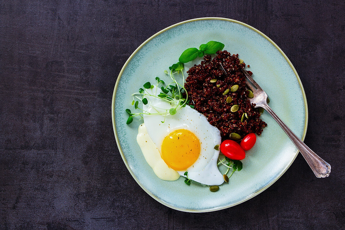 Plate of red quinoa with fried egg, sprouts, tomatoes and pumpkin seeds for healthy dinner on dark rustic slate background