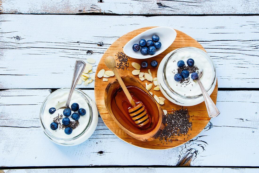 Mason jars of breakfast yogurt with chia seeds, honey and fresh blueberries on white grunge wooden background
