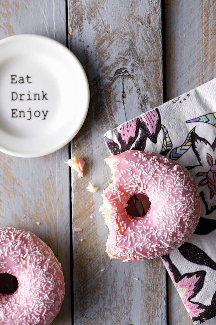 A bitten doughnut with pink frosting on a colourful napkin
