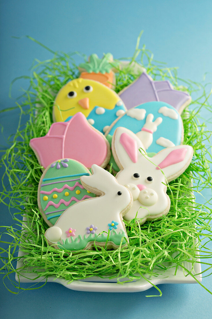 Easter cookies, bunnies and eggs on white plate with decorative grass
