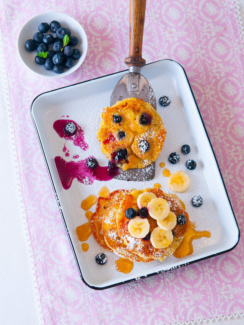 Banana and blueberry pancakes with maple syrup