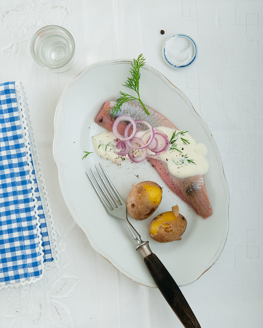 Herring with part peeled potatoes, dill sauce and onion rings