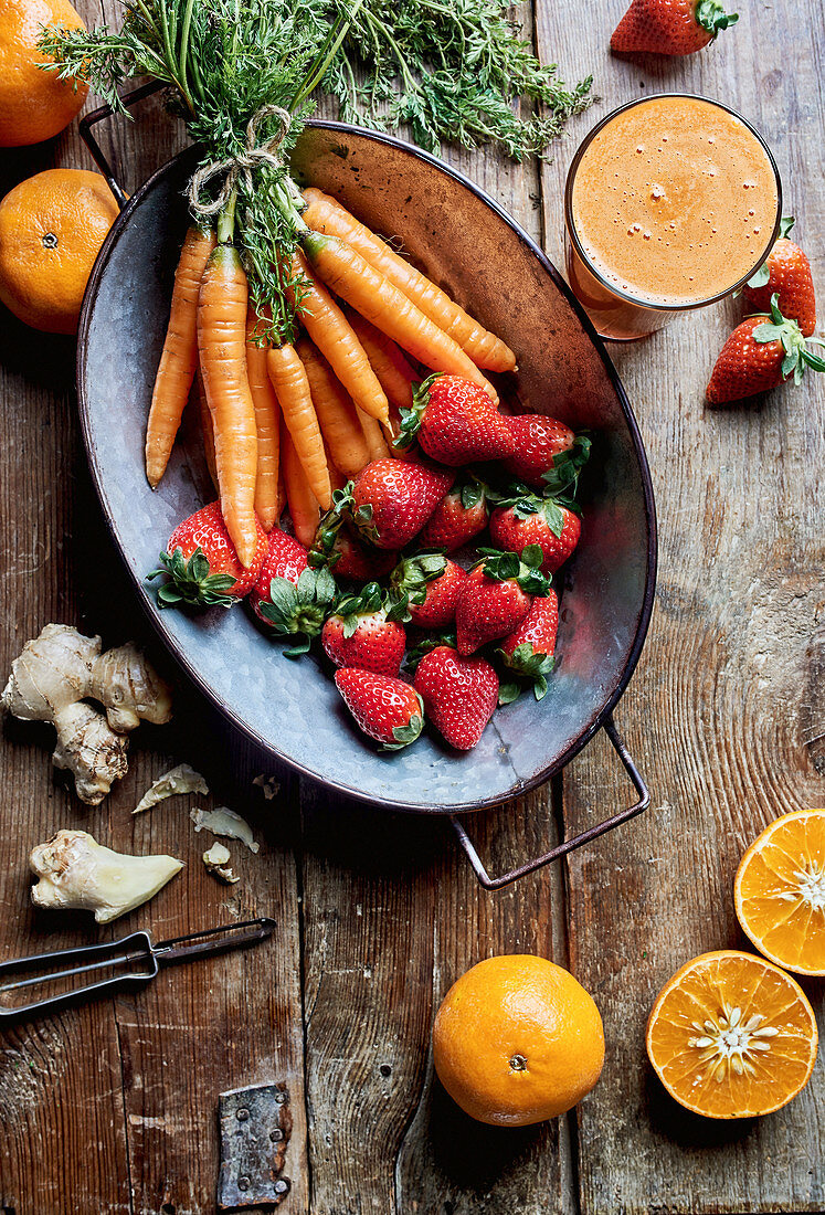 Fresh detox juice with oranges, strawberries, ginger and carrots