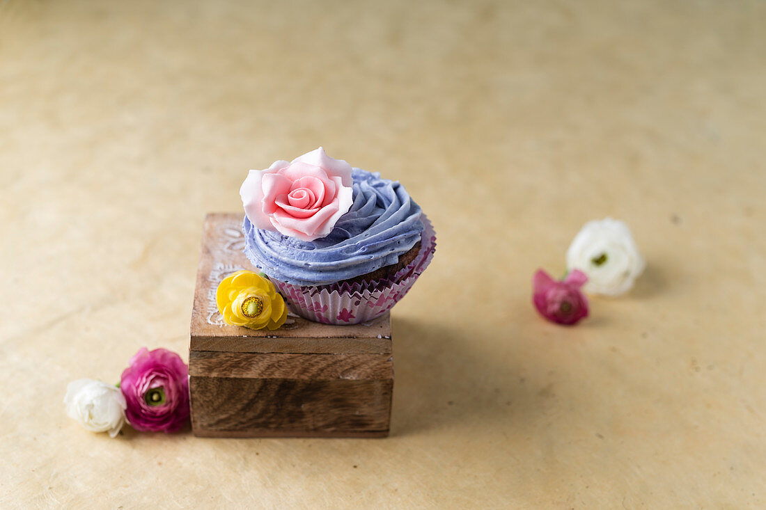 A cupcake with blue cream and a rose blossom