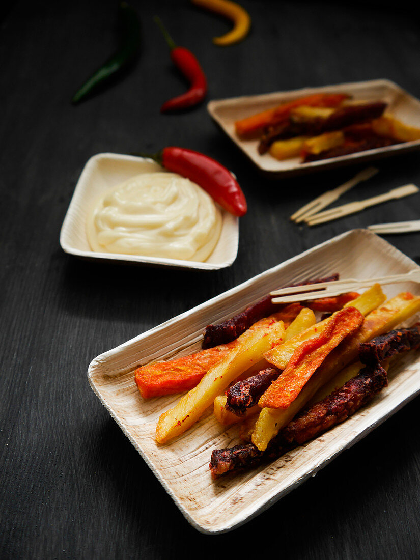 Vegetable fries on a wooden plate with mayonnaise