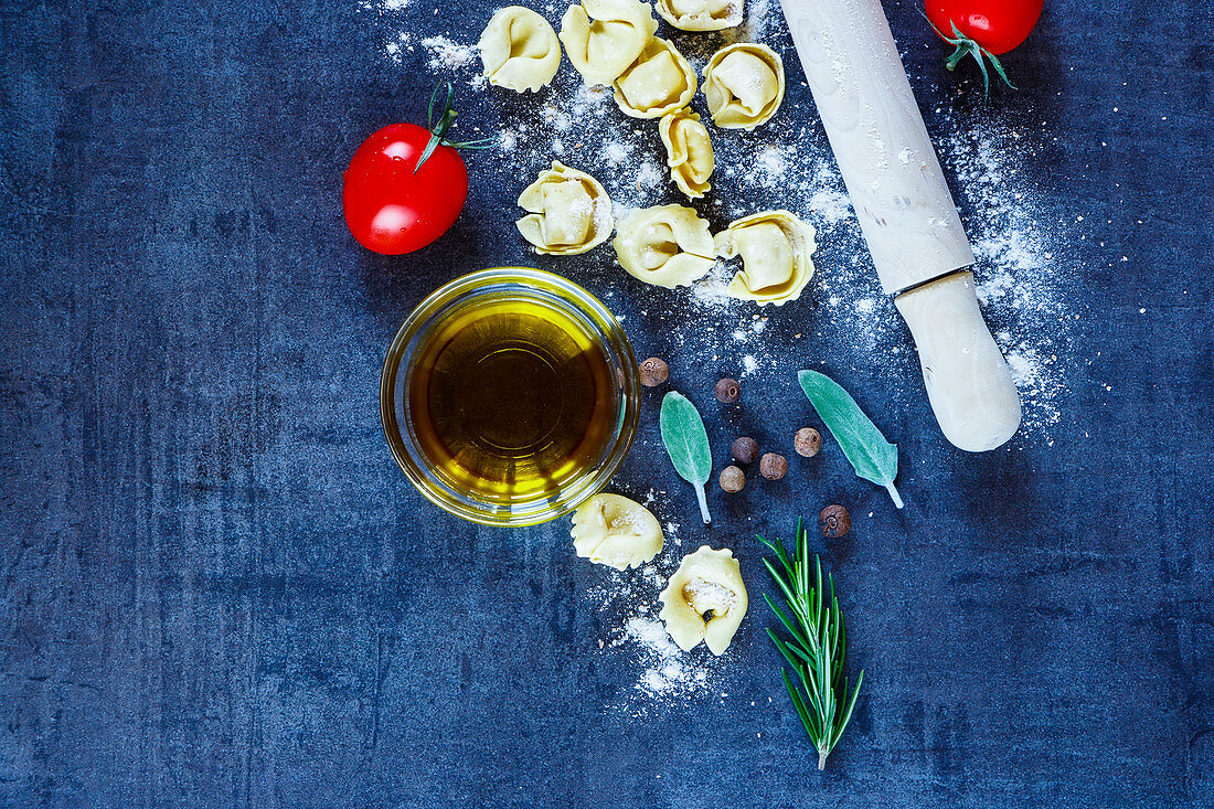 Food background with homemade Italian pasta tortellini, tomatoes, flour, fresh herbs and olive oil on dark vintage texture