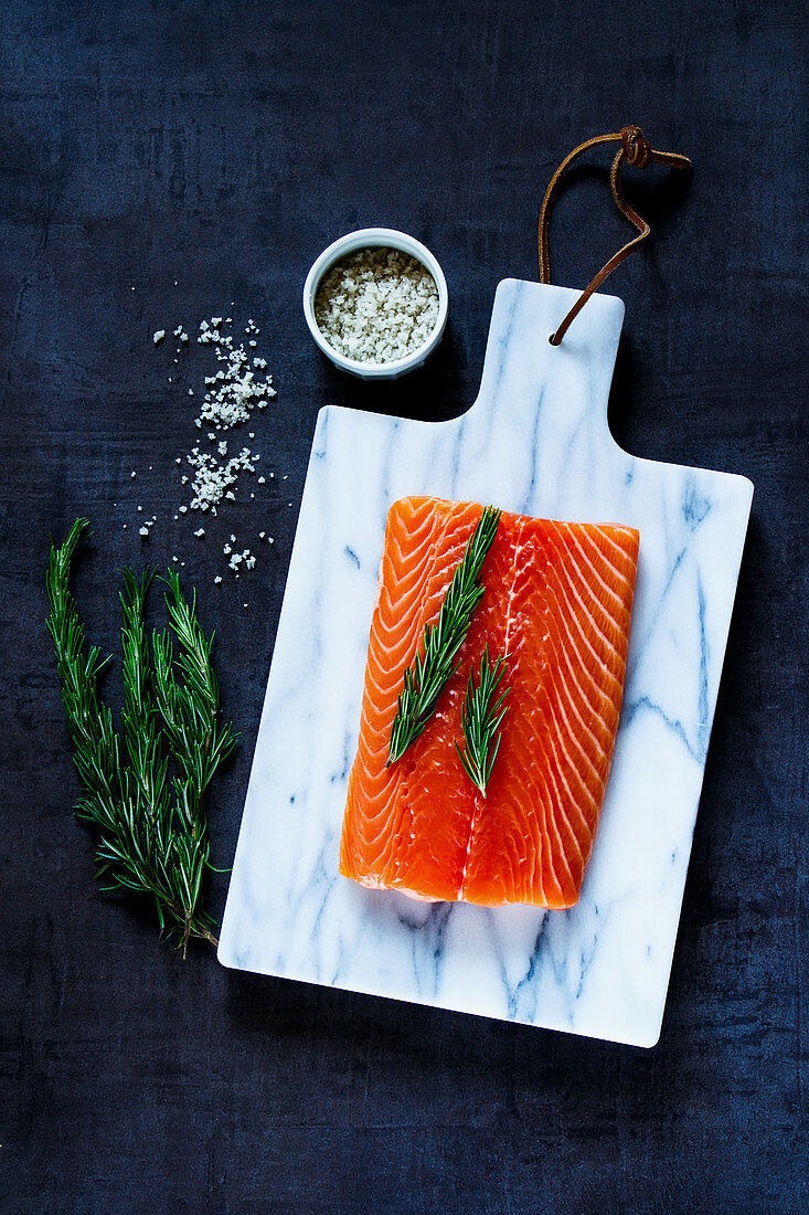Fresh raw salmon fillet with rosemary and grey salt on marbre cutting board