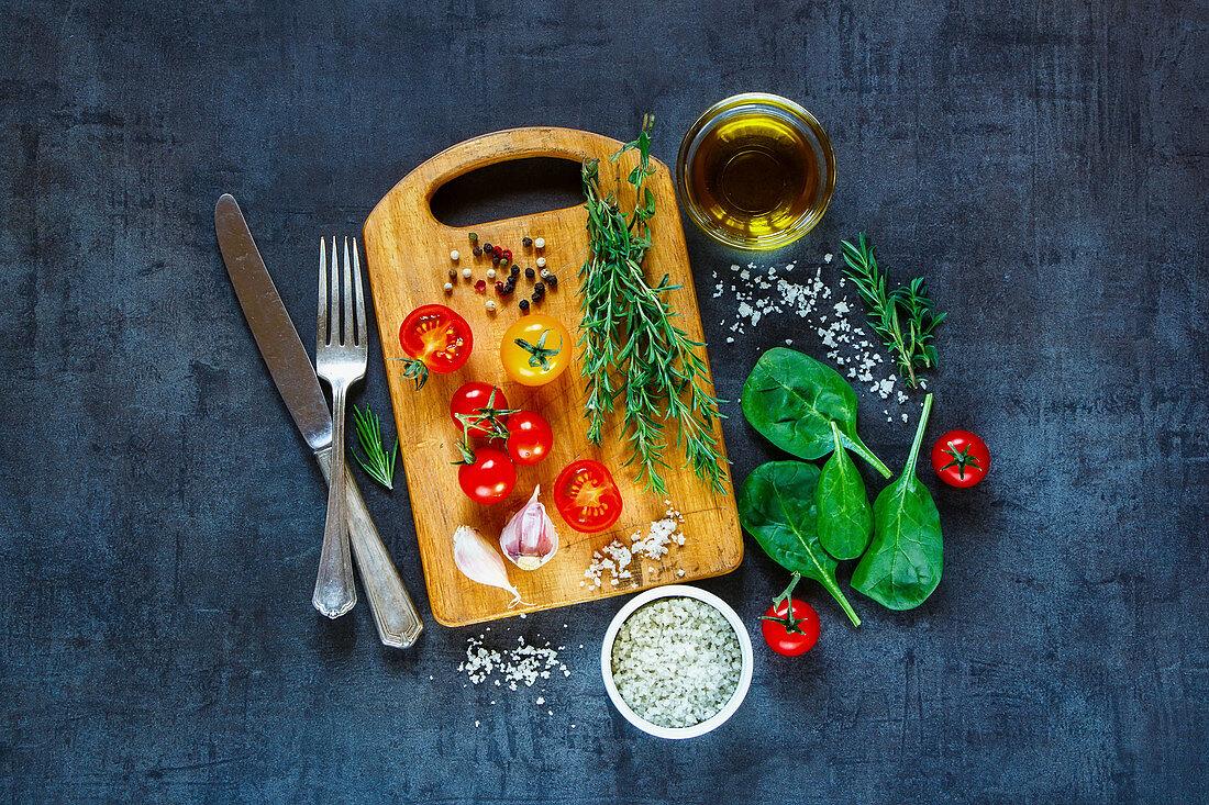 Tasty vegetarian ingredients, olive oil and seasoning on rustic wooden cutting board over dark vintage background