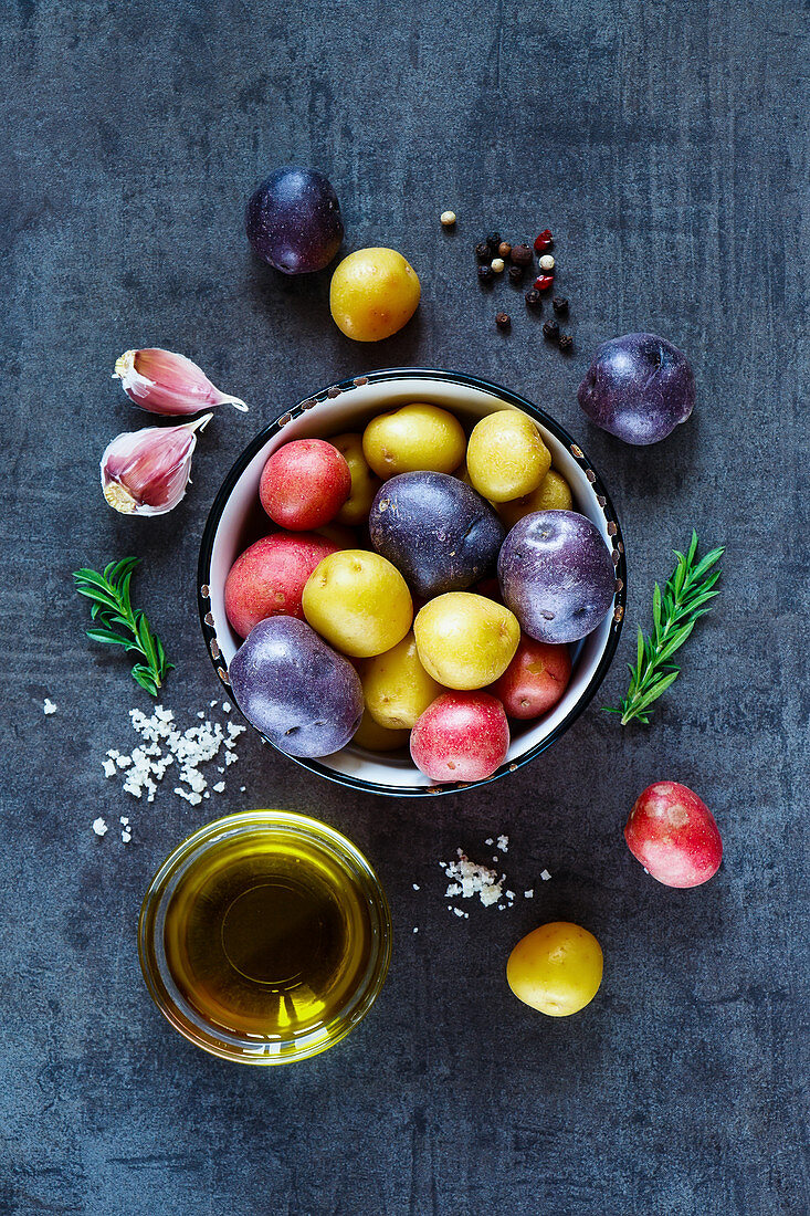 Cooking background with fresh potatoes, garlic and olive oil over dark grunge table