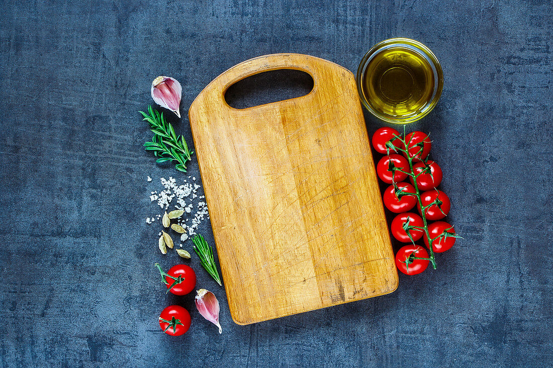 Top view of empty vintage cutting board with organic tomatoes, spices and olive oil over dark grunge background