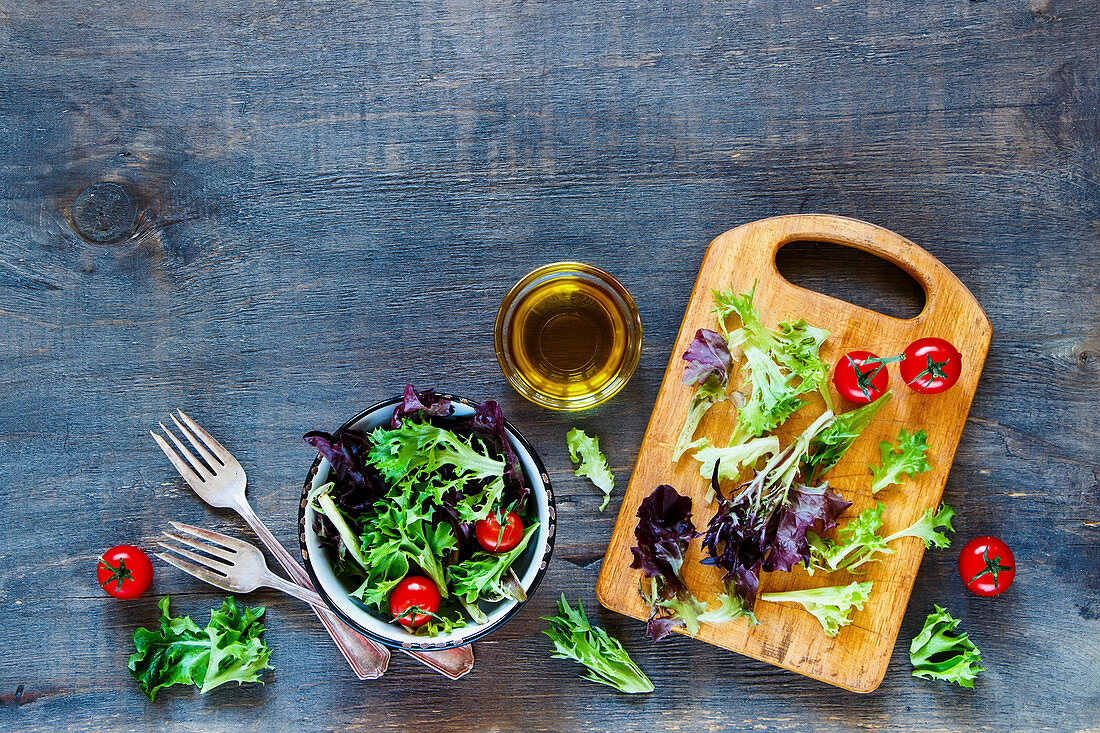 Fresh healthy salad with tomatoes in vintage bowl over rustic wooden background