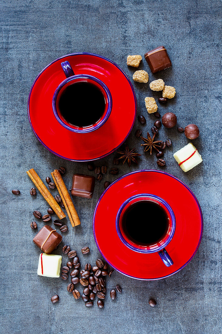 Coffee composition with two red cups, spices and chocolate on dark vintage background