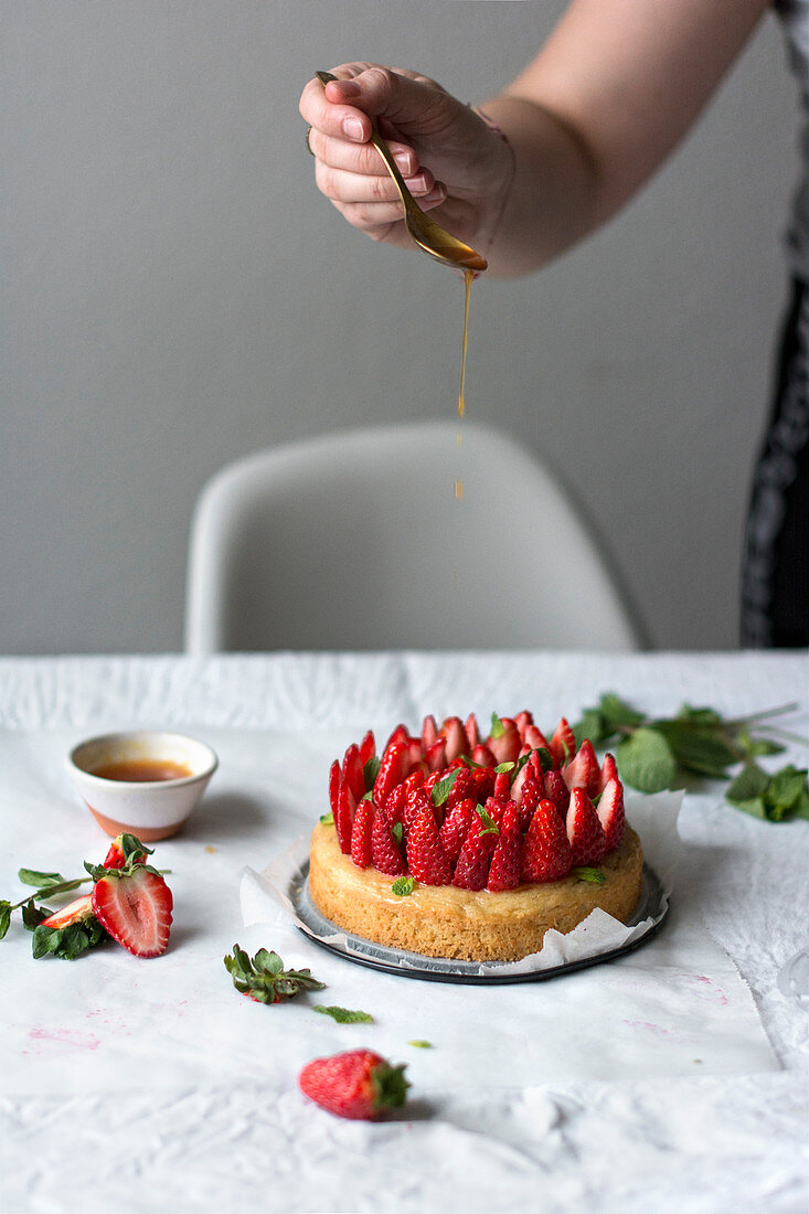 A basil cake with fresh strawberries, drizzled with mint syrup