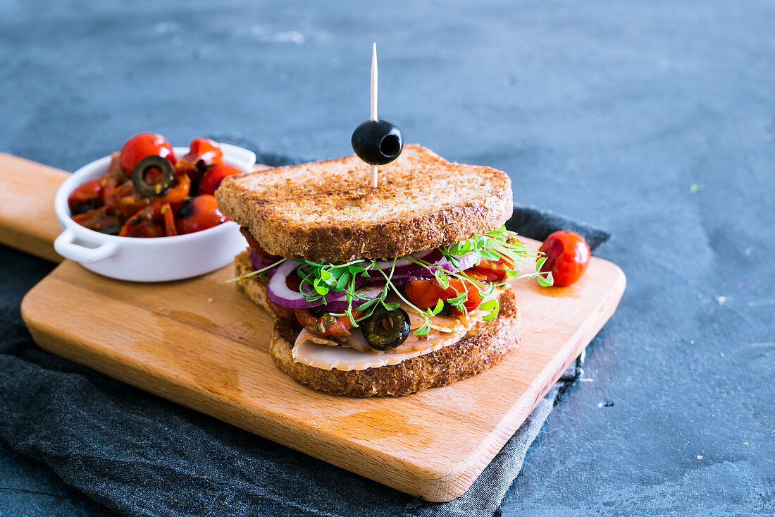 A turkey sandwich with pesto, sprouts, olives, cherry tomatoes and onions