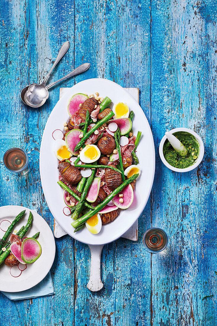 Asparagus hasselback potato radish and egg salad with pesto and hazlenuts