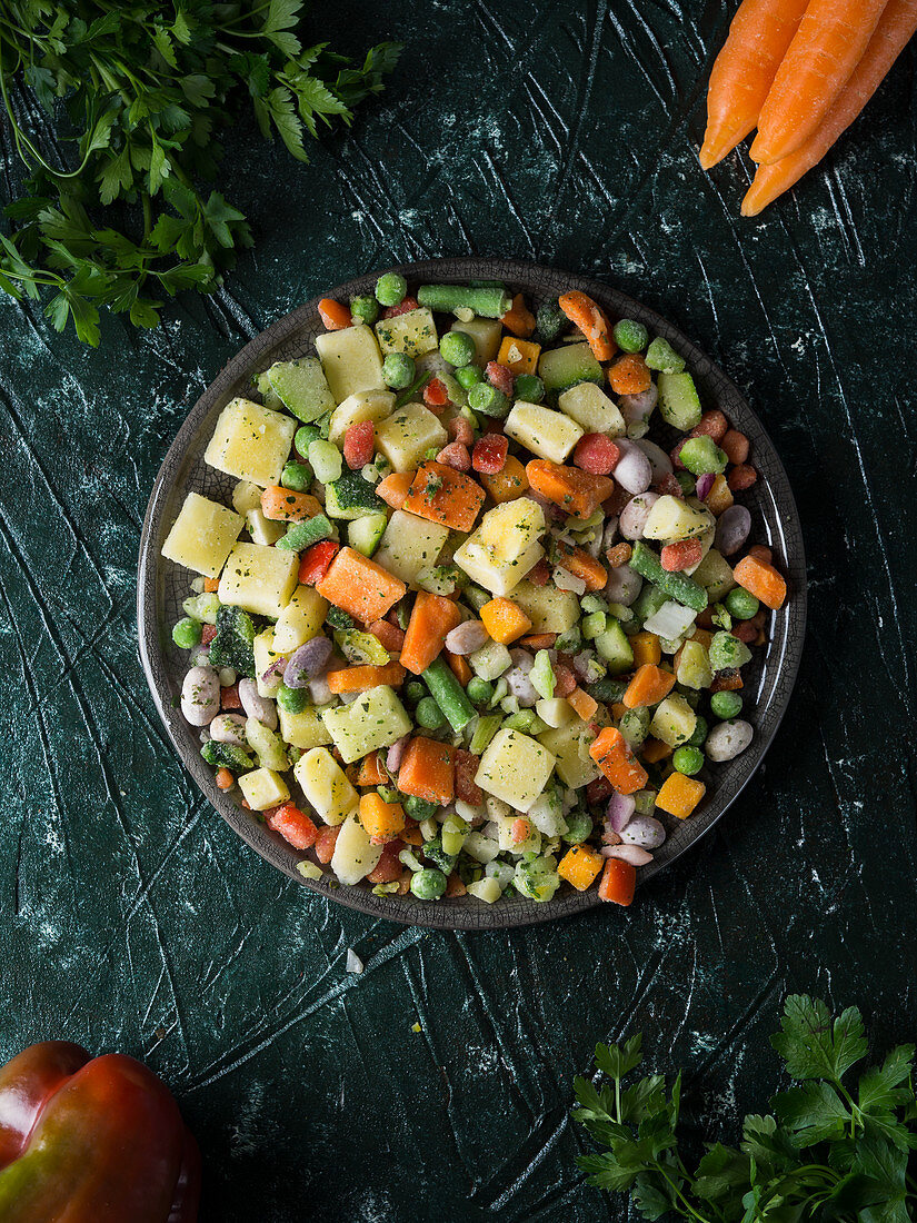 Frozen vegetables in pieces on a dish over green background